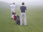 Uncle Steve hits a shot into the fog as Joe the Caddy critiques his swing.
